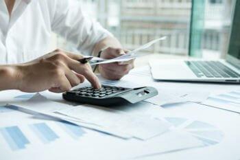 MIcroempreendedor fazendo a contabilibidade da sua MEI, fazendo calculos na calculadora e vendo um boleto