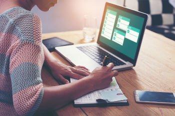 microempreendedora pesquisando no computador as atividades dos meis e tomando nota.