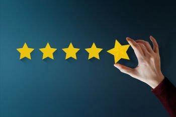 Mão segurando estrelas, fazendo a avaliação de clientes - que significa a avaliação de clientes e de como fazer a formação de carteira