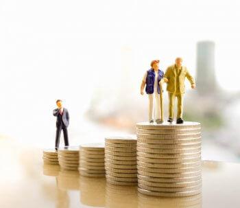 Pilha de moedas e bonecos demostrando um planejamento financeiro para a aposentadoria