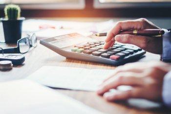 microempreendedor fazendo cálculos em uma calculadora e anotações.