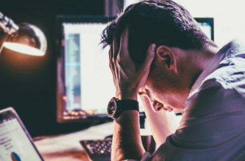 Empreendedor com as mãos na cabeça preocupado com as dívidas