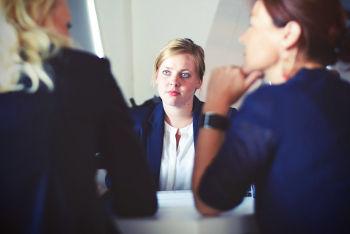 Dois empreendedores fazendo uma entrevista com candidata, que parece muito atenta e nervosa, em uma entrevista conduza-a adequadamente, ouvindo mais que falando.