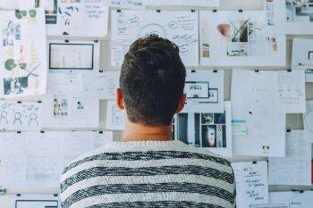 empreendedor de costas olhando uma parede com um planejamento completo do seu negócio