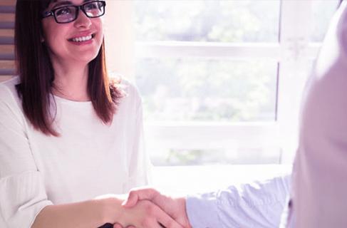 empreendedora sorrindo ao cumprimentar o seu cliente