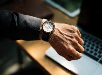 Empreendedor olhando ao relógio, o que indica que faz o calculo de custo por hora trabalhada.