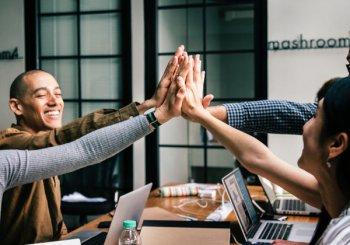 equipe de uma micro empresa motivada e comemorando suas conquistas todos de mãos juntas.