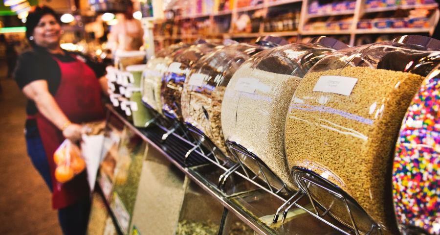 empreendedora ao fundo em sua loja de doces e cereais a granel, fazendo uma boa gestão dos recursos