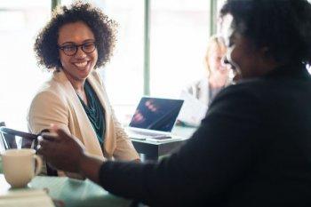empreendedora sentada a mesa conversando com uma colaboradora e tomando um cafè