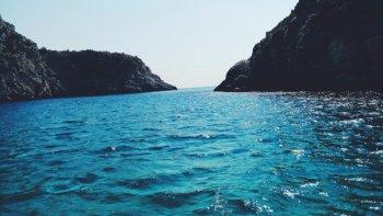 um foto de uma baia, com um mar bem azul - representa