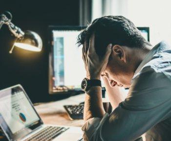 Empreendedor estressado com as mão na cabeça, demonstrando muito cansaço