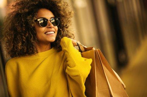 Mulher negra fazendo compraz com sacolas, black friday